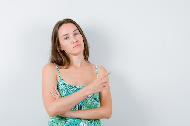Jonge dame in blouse die naar de rechterbovenhoek wijst en er zelfverzekerd uitziet, vooraanzicht.