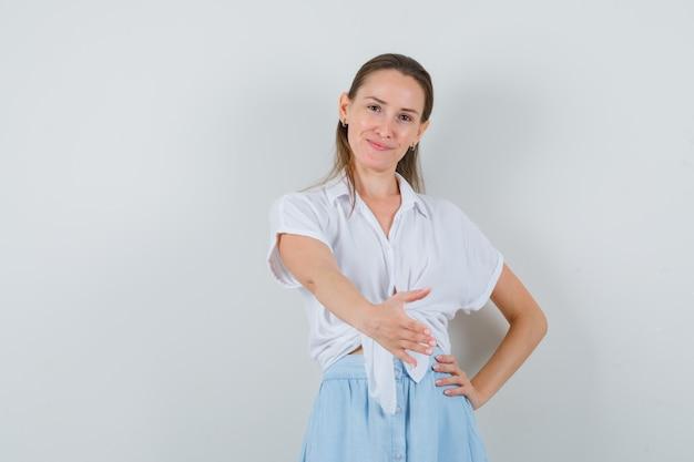 Jonge dame in blouse en rok die hand geeft om te schudden en er zachtaardig uit te zien