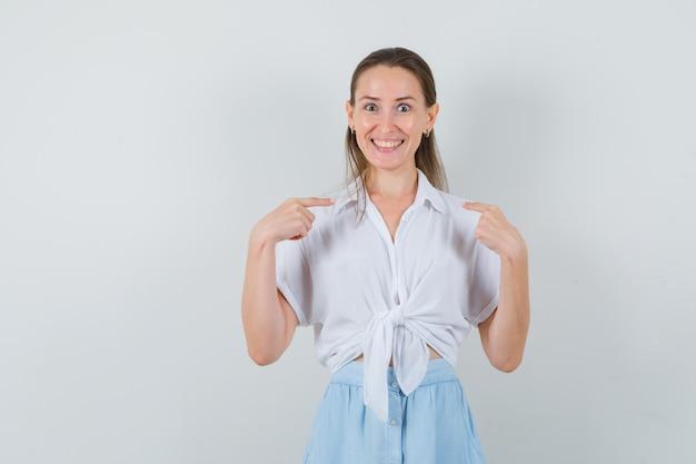 Jonge dame in blouse en rok die naar zichzelf richt en vrolijk kijkt