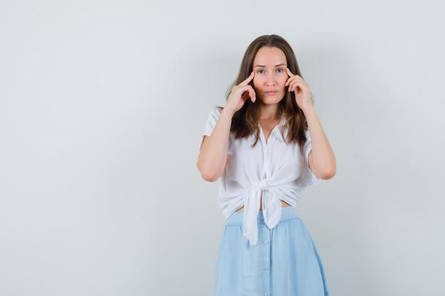 Jonge dame in blouse en rok die vingers op tempels houdt en er verstandig uitziet