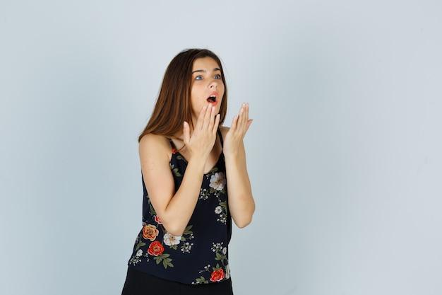 Jonge dame in blouse hand in hand in de buurt van open mond en kijkt geschokt, vooraanzicht.