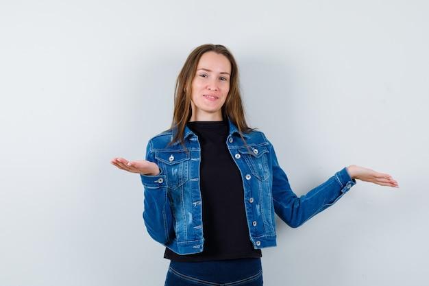Jonge dame in blouse, jas die iets presenteert of vergelijkt en er zelfverzekerd uitziet, vooraanzicht.