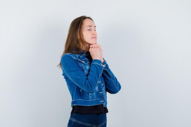 Jonge dame in blouse, jas die kin op gevouwen handen steunt en er hoopvol uitziet, vooraanzicht.