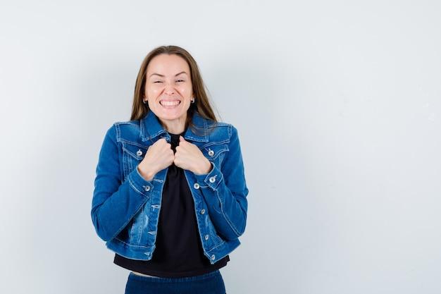Jonge dame in blouse, jas hand in hand op de borst en vrolijk kijkend, vooraanzicht.