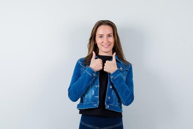 Jonge dame in blouse, jas met dubbele duimen omhoog en zelfverzekerd, vooraanzicht.