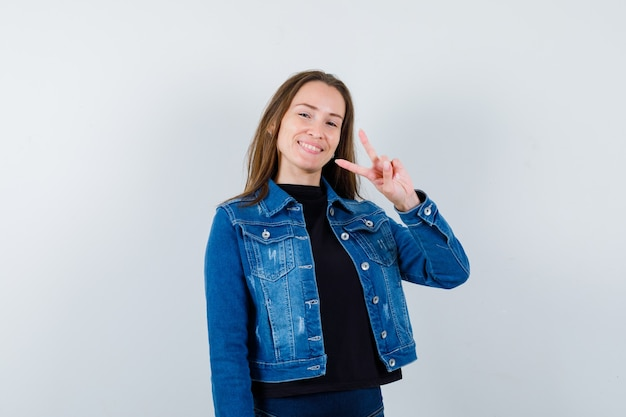 Jonge dame in blouse, jas met v-teken en vrolijk, vooraanzicht.