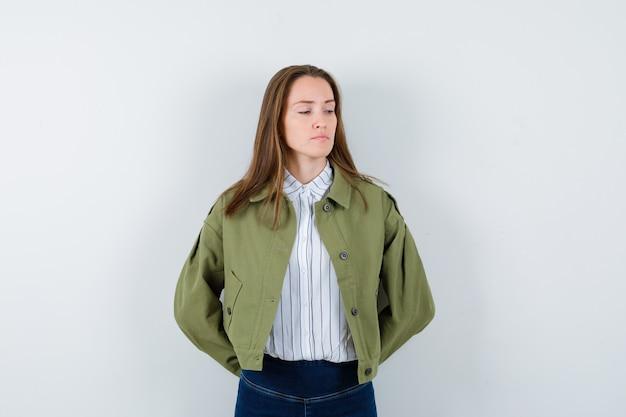 Jonge dame in blouse, jas naar beneden kijkend met de handen achter de rug en verdrietig, vooraanzicht.