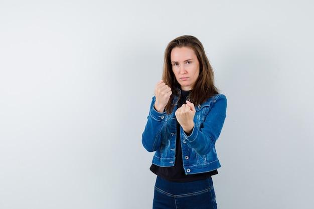 Jonge dame in blouse, jas, spijkerbroek die in gevechtshouding staat en er zelfverzekerd uitziet, vooraanzicht.