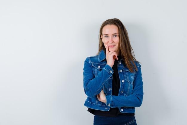 Jonge dame in blouse, jas staat in denkende pose en ziet er zelfverzekerd uit, vooraanzicht.