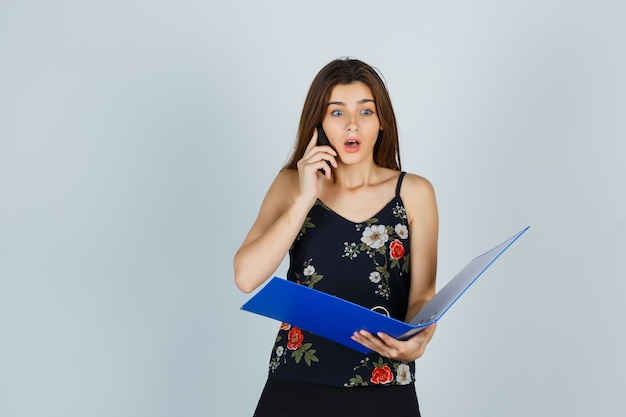 Jonge dame in blouse met map, praten op mobiele telefoon en geschokt kijken, vooraanzicht.