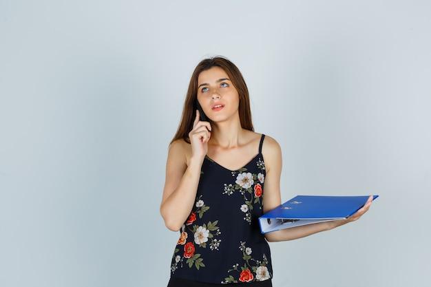 Jonge dame in blouse met map, praten op mobiele telefoon en peinzend kijkend, vooraanzicht.