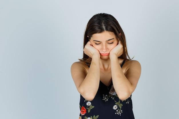 Jonge dame in blouse mokkend met wangen leunend op handen en verdrietig, vooraanzicht.