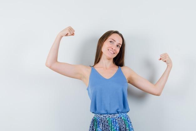 Jonge dame in blouse, rok die haar armspieren toont en energiek kijkt, vooraanzicht.