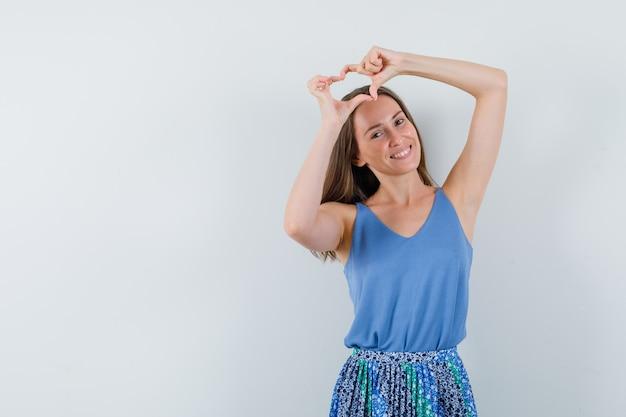 Jonge dame in blouse, rok die vredesgebaar boven het hoofd toont en gelukkig, vooraanzicht kijkt. ruimte voor tekst