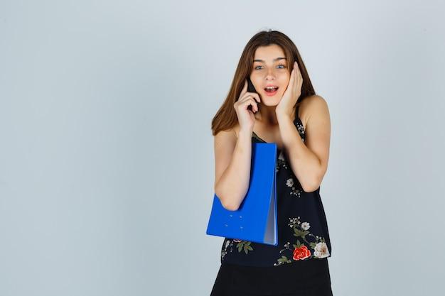 Jonge dame in blouse, rok met map, praten op mobiele telefoon, hand op wang houden en opgewonden kijken, vooraanzicht.