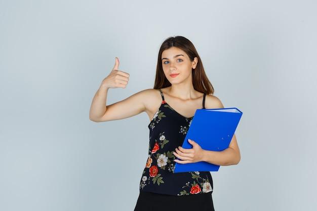 Jonge dame in blouse, rok met map terwijl ze duim omhoog laat zien en er vrolijk uitziet, vooraanzicht.