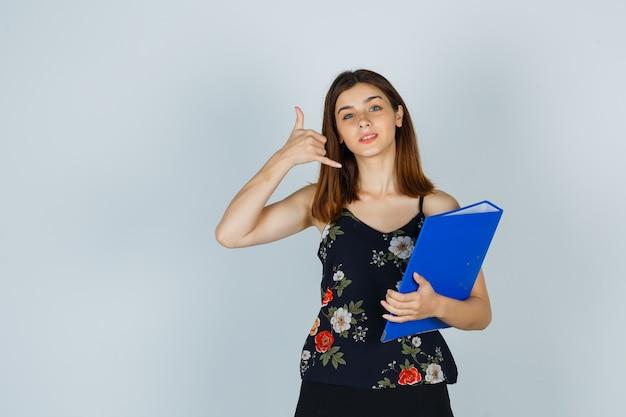 Jonge dame in blouse, rok met map terwijl ze een telefoongebaar toont en er behulpzaam uitziet, vooraanzicht.