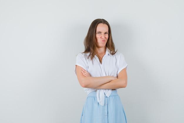 Jonge dame in blouse, rok staat met gekruiste armen terwijl ze haar lippen pruilt en er beledigd uitziet