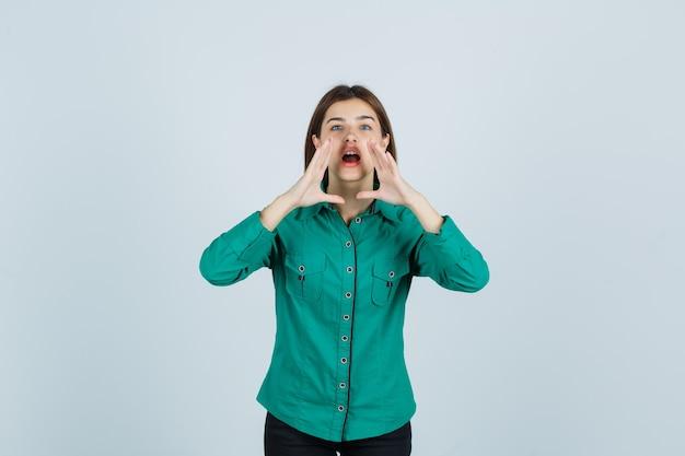 Jonge dame in een groen shirt hand in hand in de buurt van de mond terwijl ze geheim vertelt en nieuwsgierig kijkt, vooraanzicht.