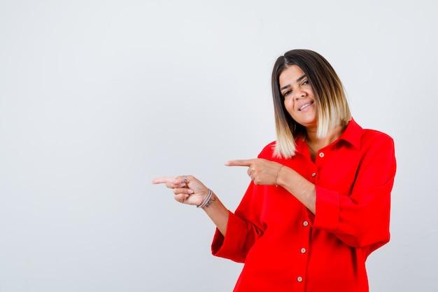 Jonge dame in een rood oversized overhemd dat naar de linkerkant wijst en er tevreden uitziet, vooraanzicht.