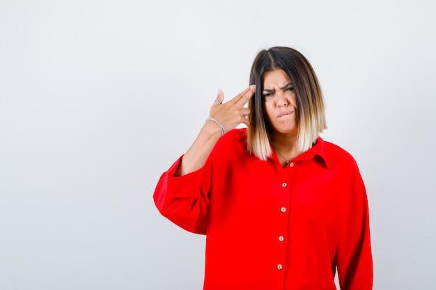 Jonge dame in een rood oversized shirt dat een pistoolgebaar toont en er serieus uitziet, vooraanzicht.