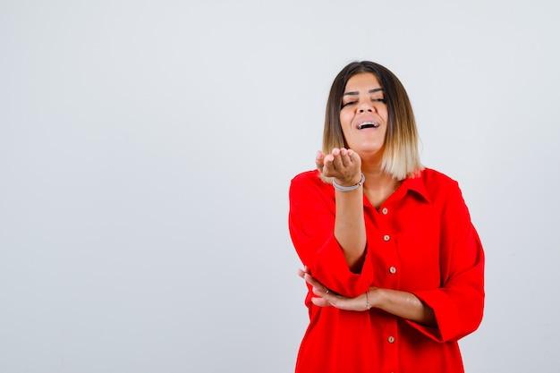 Jonge dame in een rood oversized shirt die de handen naar de camera uitstrekt en er vrolijk uitziet, vooraanzicht.