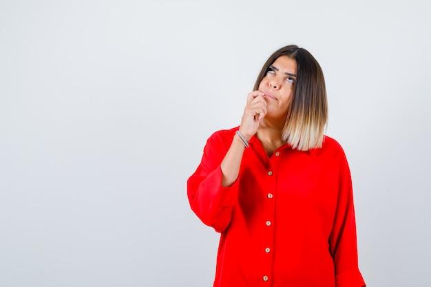 Jonge dame in een rood oversized shirt die hand in de buurt van de mond houdt en er attent uitziet, vooraanzicht.