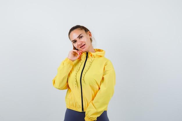 Jonge dame in geel jasje met hand dichtbij wang en aantrekkelijk, vooraanzicht.