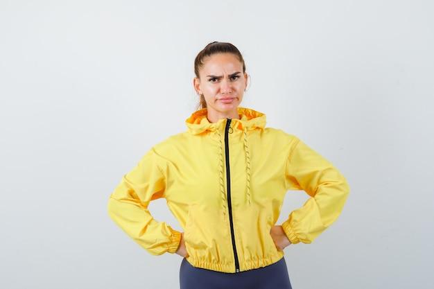 Jonge dame in geel jasje met handen op taille en ontevreden, vooraanzicht.