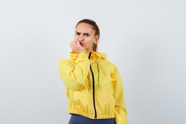 Jonge dame in gele jas die de hand op de kin houdt en er ontevreden uitziet, vooraanzicht.