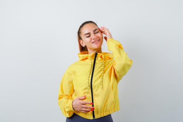 Jonge dame in gele jas die de hand op de tempel houdt, de ogen sluit en er charmant uitziet, vooraanzicht.