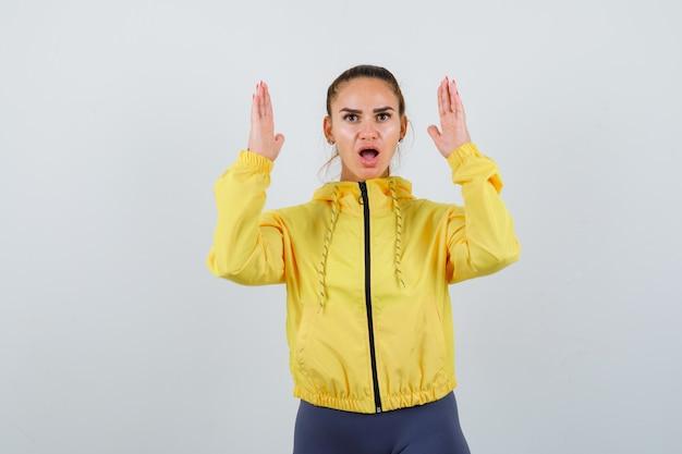 Jonge dame in gele jas die handen in overgavegebaar houdt en perplex kijkt, vooraanzicht.