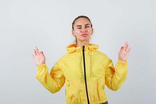 Jonge dame in gele jas die meditatiegebaar toont en er ontspannen uitziet, vooraanzicht.