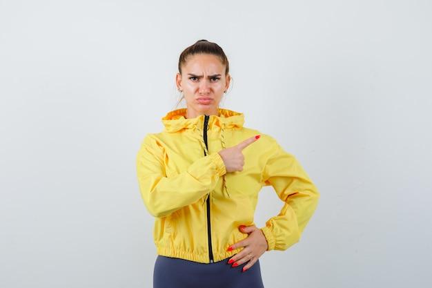 Jonge dame in gele jas die naar de rechterbovenhoek wijst en er serieus uitziet, vooraanzicht.