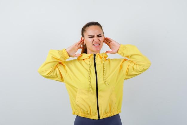 Jonge dame in gele jas die oren stopt met vingers en er geïrriteerd uitziet, vooraanzicht.