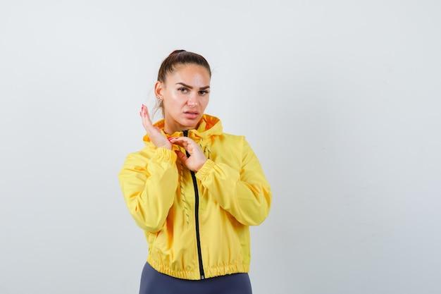 Jonge dame in gele jas die palm krabt en ontevreden kijkt, vooraanzicht.