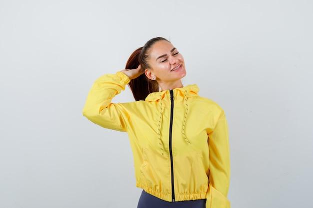 Jonge dame in gele jas die zich voordeed terwijl ze haar oren regelde en er aantrekkelijk uitzag, vooraanzicht.