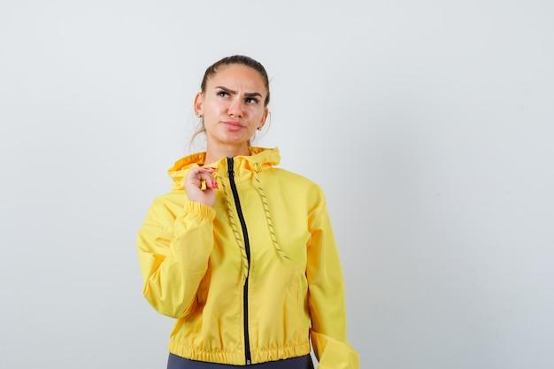 Jonge dame in gele jas met hand over borst en peinzend, vooraanzicht.