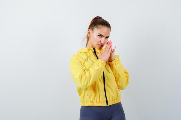Jonge dame in gele jas met handen in biddend gebaar en attent, vooraanzicht.