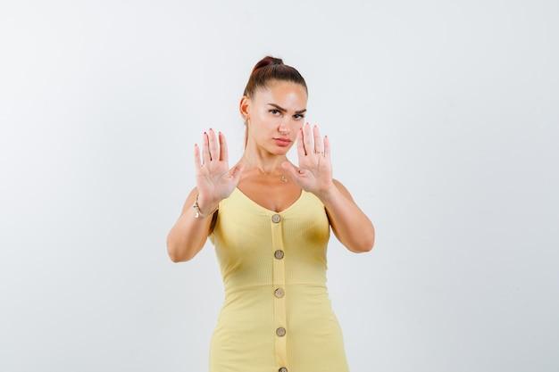 Jonge dame in gele jurk die stopgebaar toont en kalm, vooraanzicht kijkt.