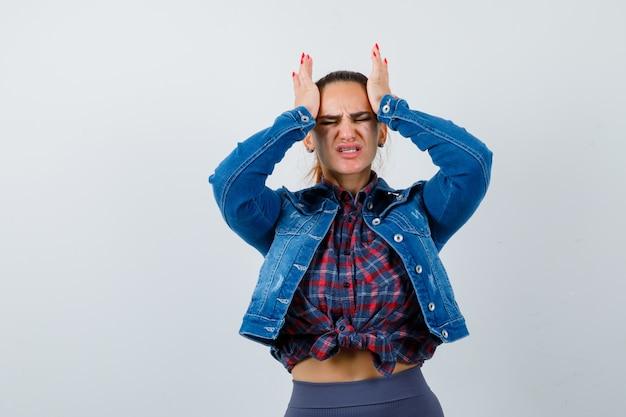 Jonge dame in geruit hemd, spijkerjasje met hoofdpijn en ziet er pijnlijk uit, vooraanzicht.