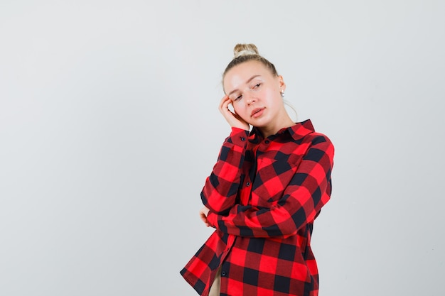Jonge dame in geruit overhemd, broek die weg kijkt en nadenkend kijkt