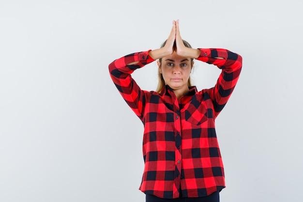 Jonge dame in geruit overhemd dat namaste-gebaar toont en er zelfverzekerd uitziet
