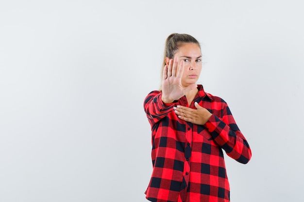 Jonge dame in geruit overhemd dat stopgebaar toont en ernstig kijkt
