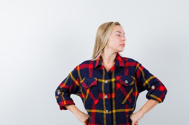 Jonge dame in geruit overhemd die de handen op de taille houdt terwijl ze wegkijkt en zelfverzekerd kijkt, vooraanzicht.
