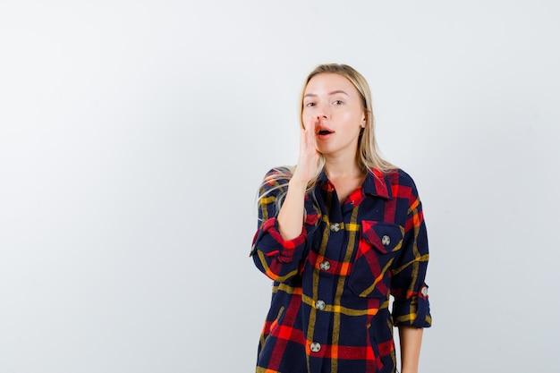 Jonge dame in geruit overhemd die geheim met hand vertelt en ernstig, vooraanzicht kijkt.