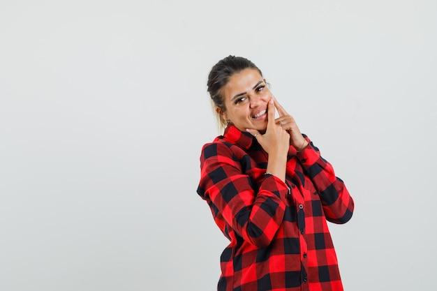 Jonge dame in geruit overhemd die haar puistje op wang knijpt en blij kijkt