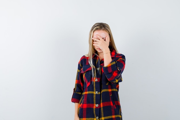 Jonge dame in geruit overhemd die hand op gezicht houden en moe, vooraanzicht kijken.