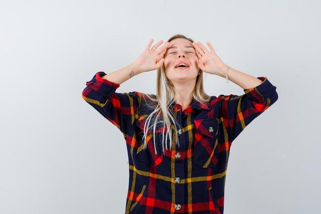Jonge dame in geruit overhemd die handpalmen op gezicht toont en vredig, vooraanzicht kijkt.