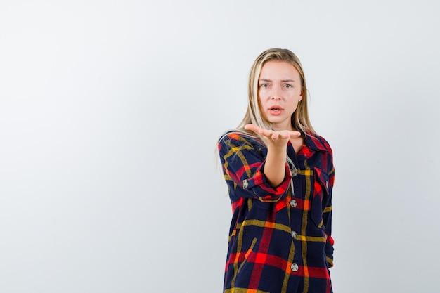 Jonge dame in geruit overhemd die iets vasthoudt en verbaasd kijkt, vooraanzicht.